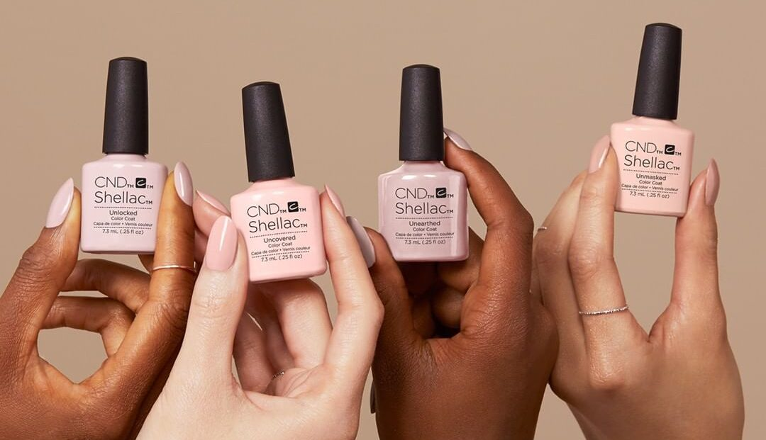 four women of different skin colours holding varying shades of nude Shellac nail polishes